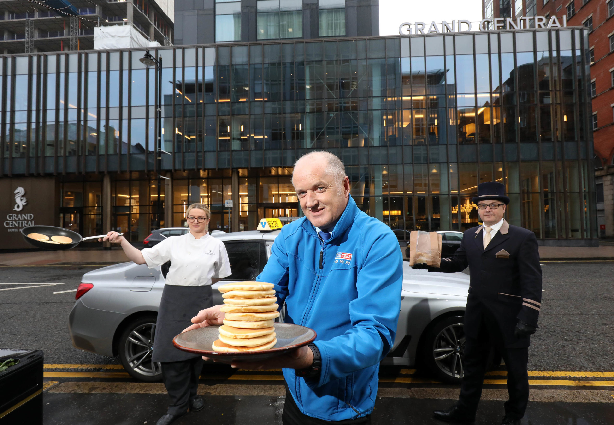 Martin Donnelly from Value Cabs is pictured with Grand Central Hotel's Pastry Chef, Caitlin Lopes, and Commissionaire, John Dodd, as the hotel gets ready to provide complimentary freshly made pancakes today for key health workers and passing taxi drivers to takeaway for Pancake Tuesday. Whilst the majority of hospitality remains closed, the Grand Central Hotel in Belfast is open for key workers and is inviting those passing by on Tuesday to enjoy some takeaway treats.